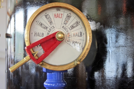 engine room: Close up of an old fashioned speed indicator and telegraph used to convey speed control orders from a ship s bridge or wheelhouse to its engine room; on historic paddle steamer Goethe on the Rhine, Germany