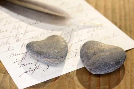 carta de amor: Dos corazones de piedra con la pluma y la letra de edad Foto de archivo
