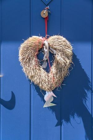 Decorative heart from straw on blue door in Svaneke on Bornholm  Denmark Stock Photo - 22141987
