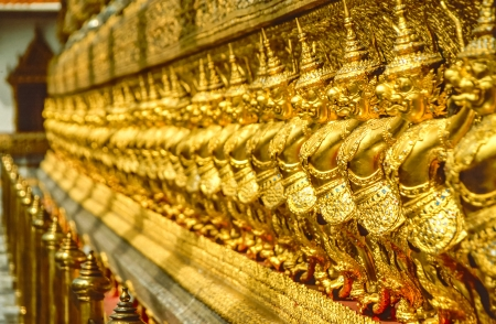 Golden row of Buddhist temple keepers at Grand Palace in Bangkok, Thailand photo