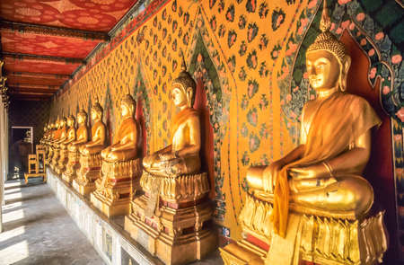 Row of golden Buddhas in Thai temple in the Grand Palace in Bangkok photo