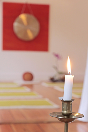 yoga pillows: Large Gong, candle and orchid decoration in a yoga room