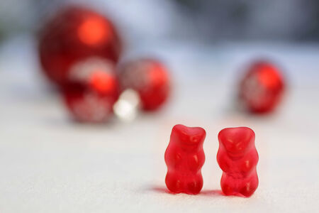 Two red gummy bears with red baubles on a white table cloth photo