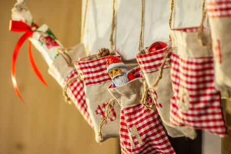 Bags of an advent calendar hanging on the fireplace Stock Photo