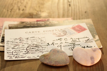 love proof: Two dark stone hearts with old French  postcard on wooden desk Stock Photo