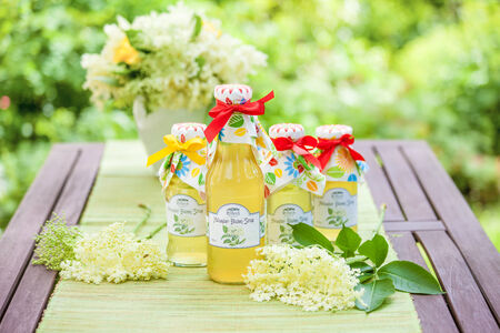 country house style: Bottles with elderflower syrup in the garden