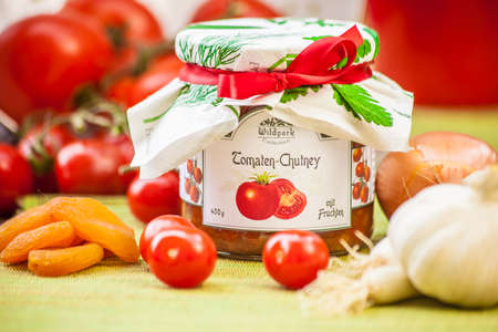chutney: Glass with tomato chutney and decoration in the garden