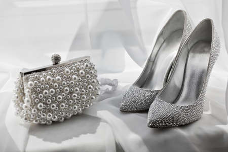 glitter silver shoes and clutch bag on white Foto de archivo