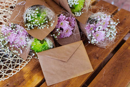 envelope decoration: Envelope and flower bouquet on the wooden table Stock Photo