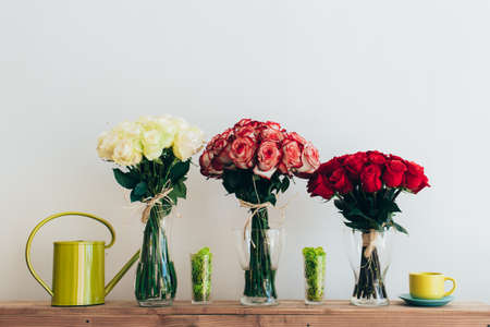 Bouquets Of Roses In Three Glass Vases Next To A Watering Can