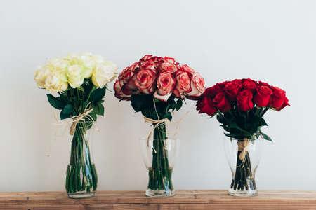 bouquet fleurs: Bouquets de roses dans les vases en verre de trois à côté d'un arrosoir sur un mur blanc