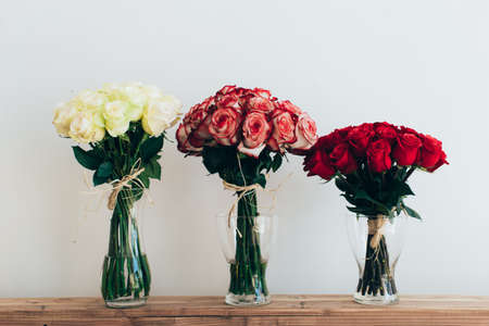 flowers bouquet: Bouquets of roses in three glass vases next to a watering can on a white wall