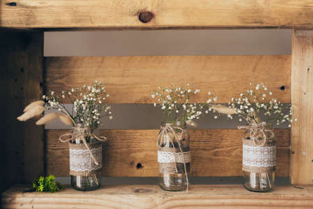 Gypsophila three jars standing on a wooden shelf