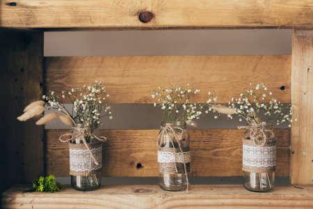 Gypsophila three jars standing on a wooden shelf