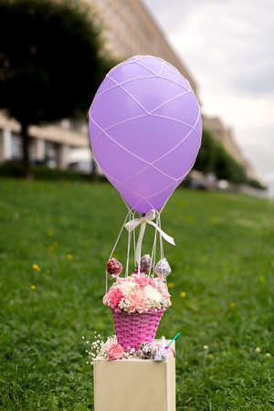 balloon bouquet: Bouquet of carnation flowers and sweets on a balloon Stock Photo