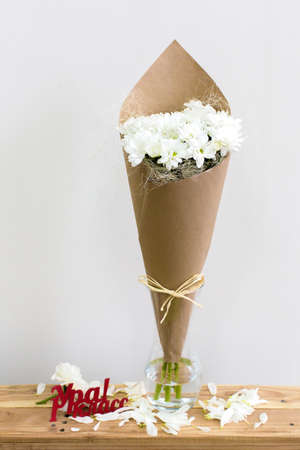 hooray: Paper cornet with a bouquet of white chrysanthemum in a glass vase. Hooray! First grade