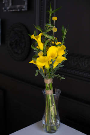 callas: Bunch of yellow callas in the vase on black background