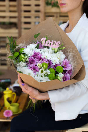 girl love: Paper cornet lisianthuses bouquet in hands of the girl. Love