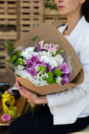 cornet: Paper cornet lisianthuses bouquet in hands of the girl. Love