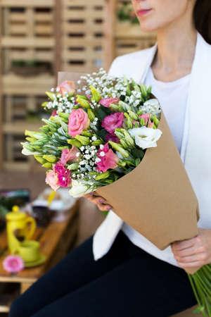 cornet: Paper cornet lisianthuses bouquet in hands of the girl Stock Photo