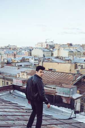 high view: Man in a leather jacket on a rooftop in the center of the city Stock Photo