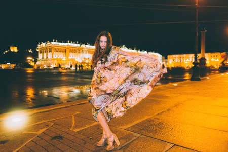 shop tender: Beautiful woman in gorgeous dress against the backdrop of the city at night. Motion effect.