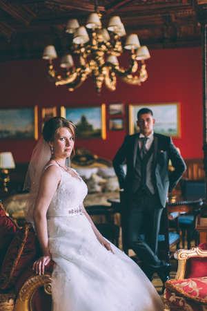 interiors: Happy bride and groom in luxury chairs in chic interiors of wedding palace