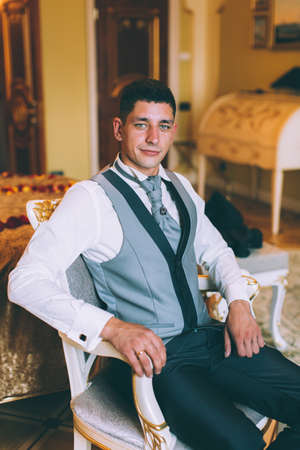 plastron: Businessman in a waistcoat and plastron sitting on a chair in the interior Suites Stock Photo