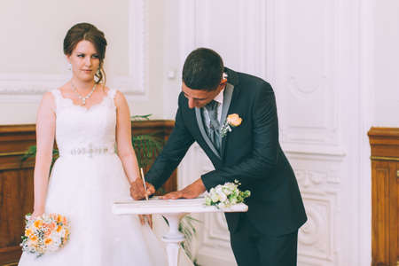 marriage: Bride and groom signing marriage license on wedding contract