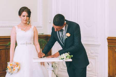 mariage: Bride et la signature de marié licence de mariage sur le contrat de mariage