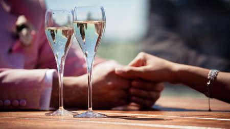泡と恋人、シャンパンのグラスを保持する互いの手のクローズ アップ