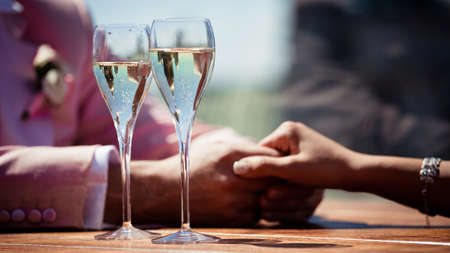 Glasses of champagne with bubbles and lovers, and that hold each others hands closeup