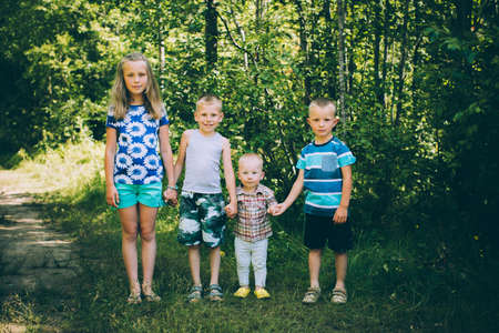 amicable: Four amicable children: One girl and three boys holding hands Stock Photo