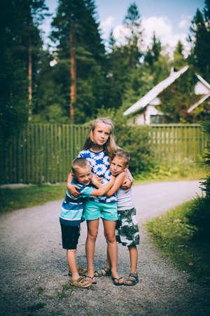 three children: Three children: Two boys hugging a girl