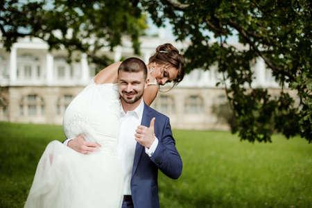 over the shoulder: Groom carries his bride over shoulder. Outdoor.