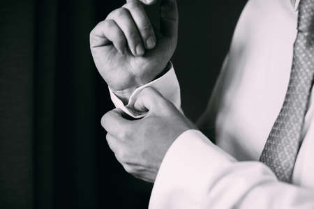 cufflink: Man buttoning on the sleeve of his shirt. Zip up the cufflink. Mens style.