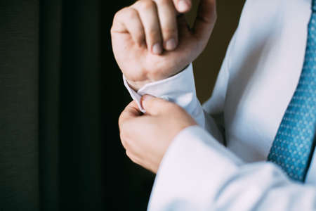 Man buttoning on the sleeve of his shirt. Zip up the cufflink. Mens style.
