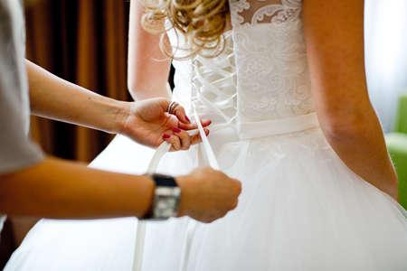 satin dress: Closeup toned photo of beautiful bride tying up her wedding dress Stock Photo