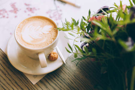 一杯のコーヒーと木製のテーブルの上に花のある静物。 写真素材