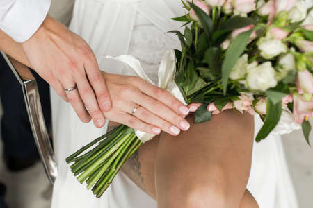 fingers put together: Hands with rings Groom putting golden ring on brides finger during wedding ceremony Stock Photo