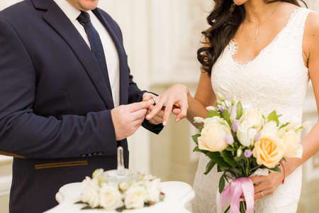 registro: Newlyweds exchange rings, groom puts the ring on the brides hand in marriage registry office