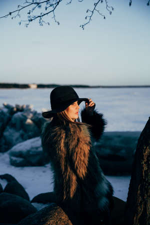 careless: Elegant girl in fur coat and hat at sunset against frozen sea Stock Photo