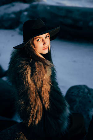 Portrait of a young beautiful blonde woman with hat, in a fur coat, outside, on the snow. A good dark day with beautiful shadows - a sunny winter day, sunset. Stock Photo