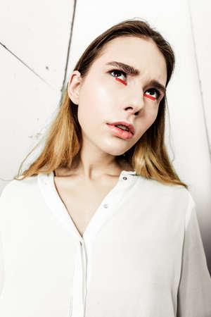 白い背景に白いシャツを着た若い美しい深刻な黒髪の女性を肖像。