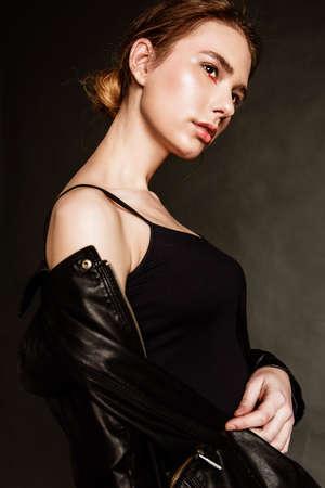 灰色のスタジオの壁に対してポーズ革の服を着たセクシーなブロンドの女性