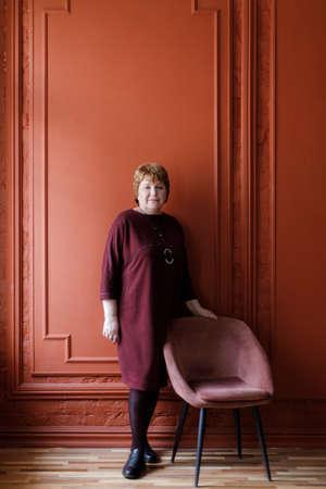 Elderly woman in a wine dress on a background of an orange wall