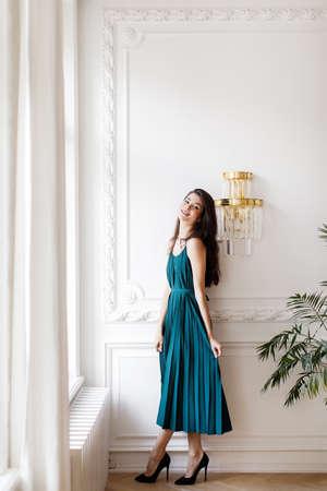 Brunette girl in a long green dress stands near a light wall Stock Photo