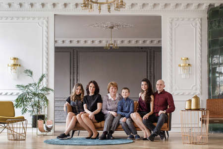 Caucasian large family sitting on a sofa in the living room in modern style