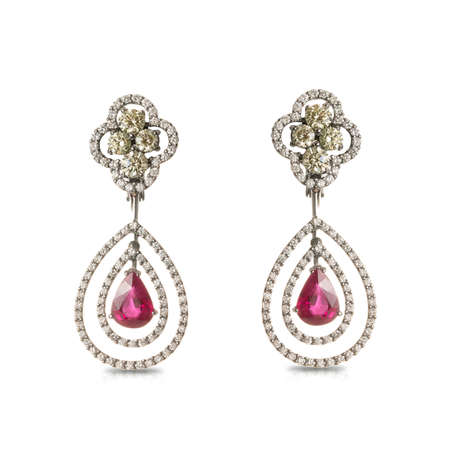Silver earrings in white gold with white and yellow diamonds and rubies in the form of a drop isolated on a white background