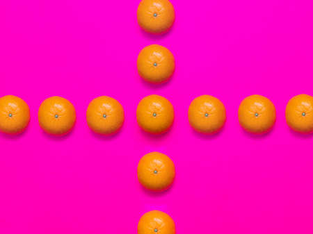 Colorful fruit pattern of fresh mandarins on a pink background. Top view